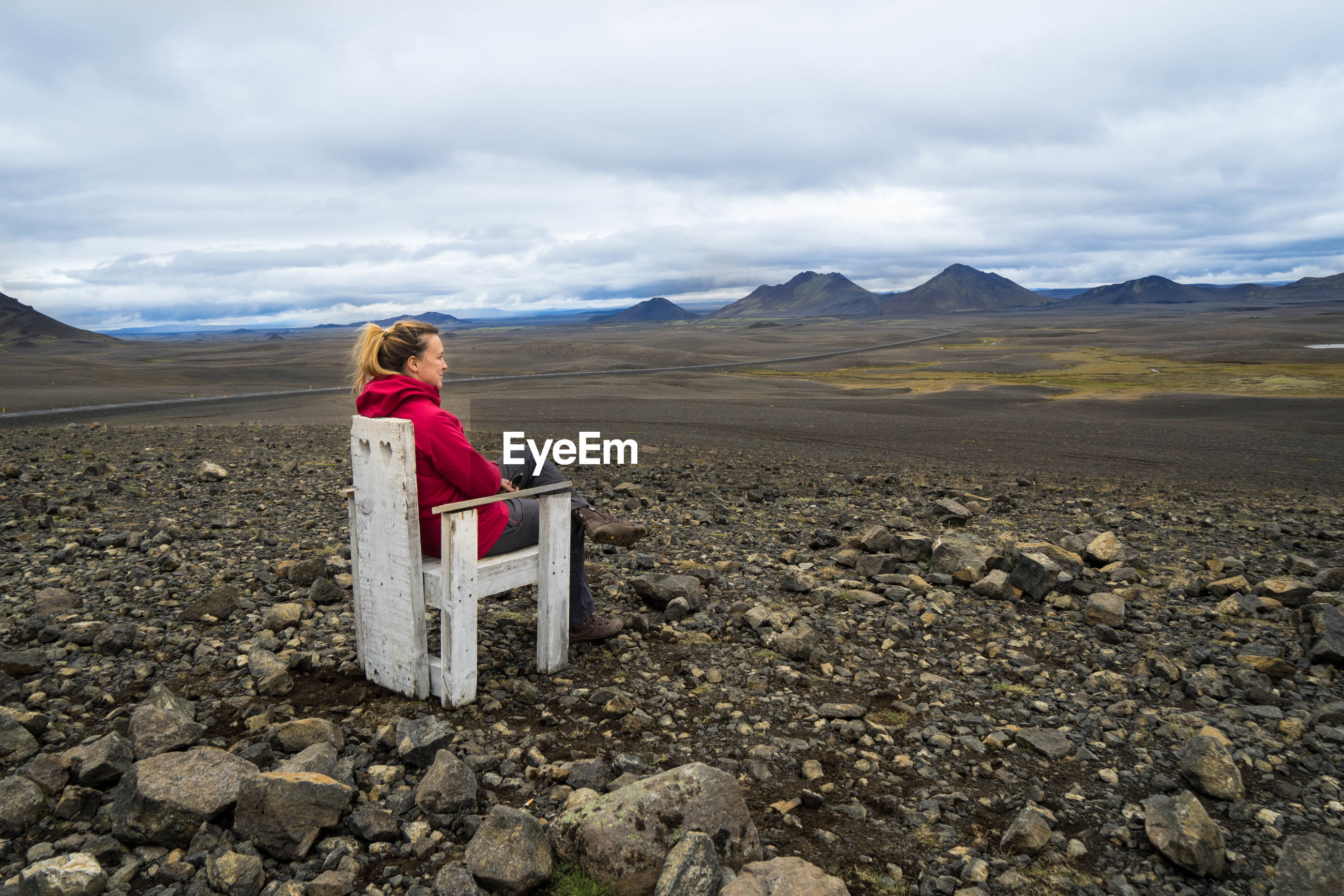 Woman sitting on chair over land against sky