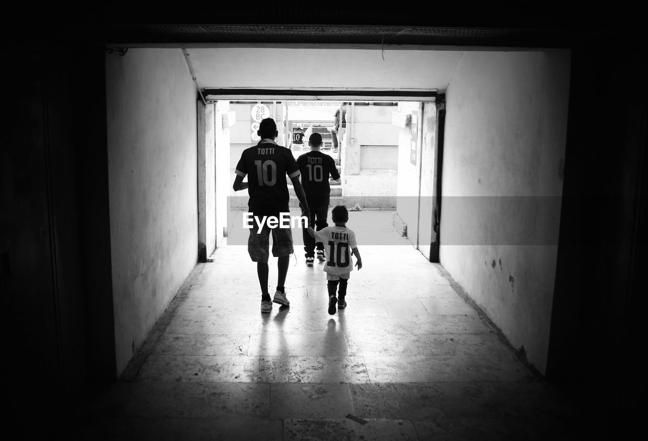 Rear view of father and son walking towards soccer stadium