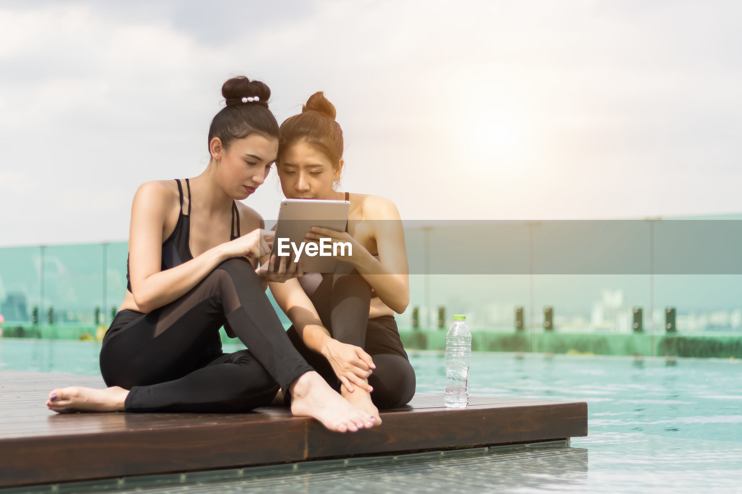 Young female using digital tablet while sitting on poolside against sky