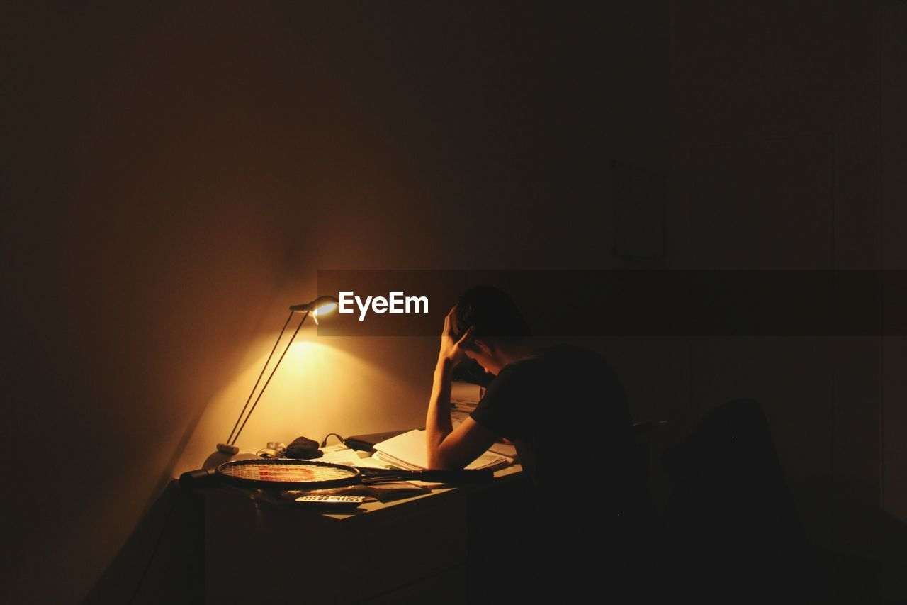 Teenager Studying In Dark At Home