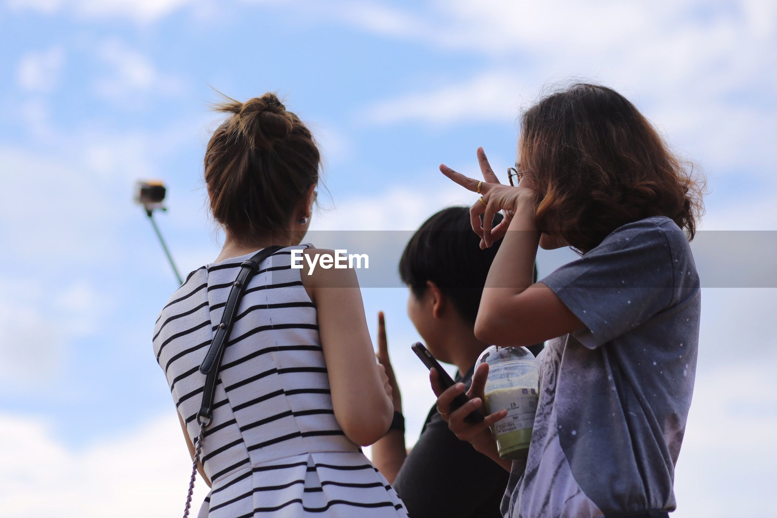Woman taking selfie with friends against sky