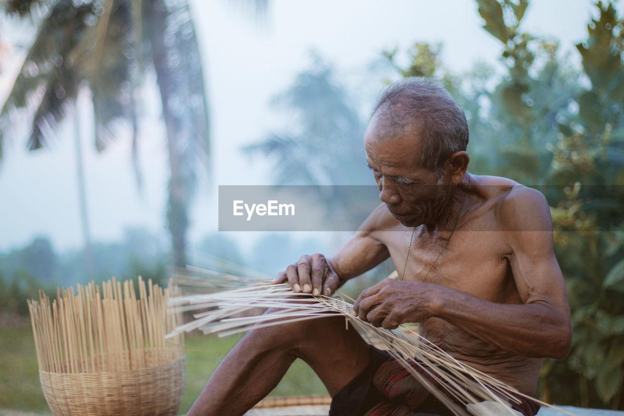 Shirtless Man Weaving Wicker Basket Against Trees