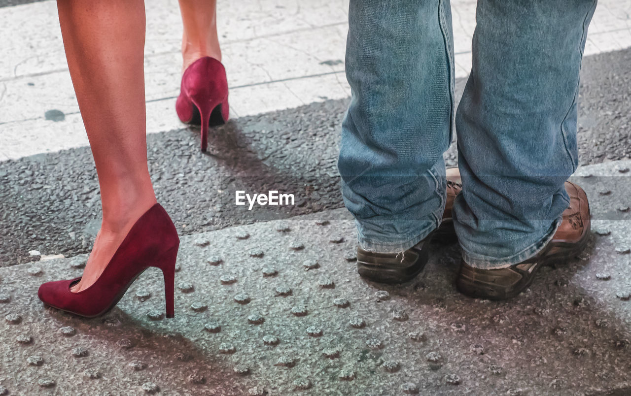 low section, human leg, human body part, shoe, body part, red, standing, women, people, high heels, real people, two people, day, men, fashion, lifestyles, adult, footpath, city, human foot, outdoors, human limb, jeans