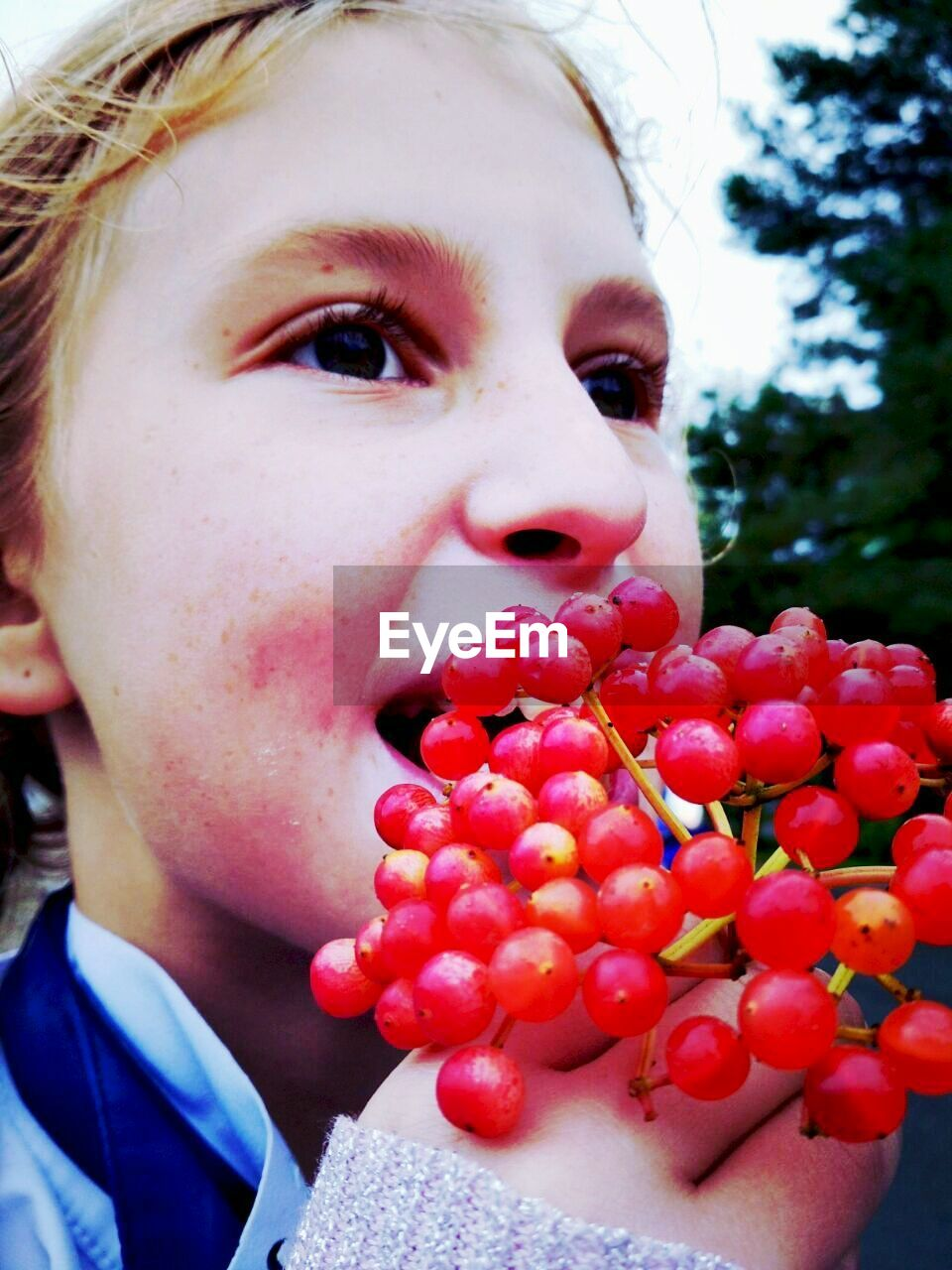 fruit, food and drink, real people, food, healthy eating, focus on foreground, childhood, close-up, one person, outdoors, freshness, day, red, lifestyles, eating, sweet food, people