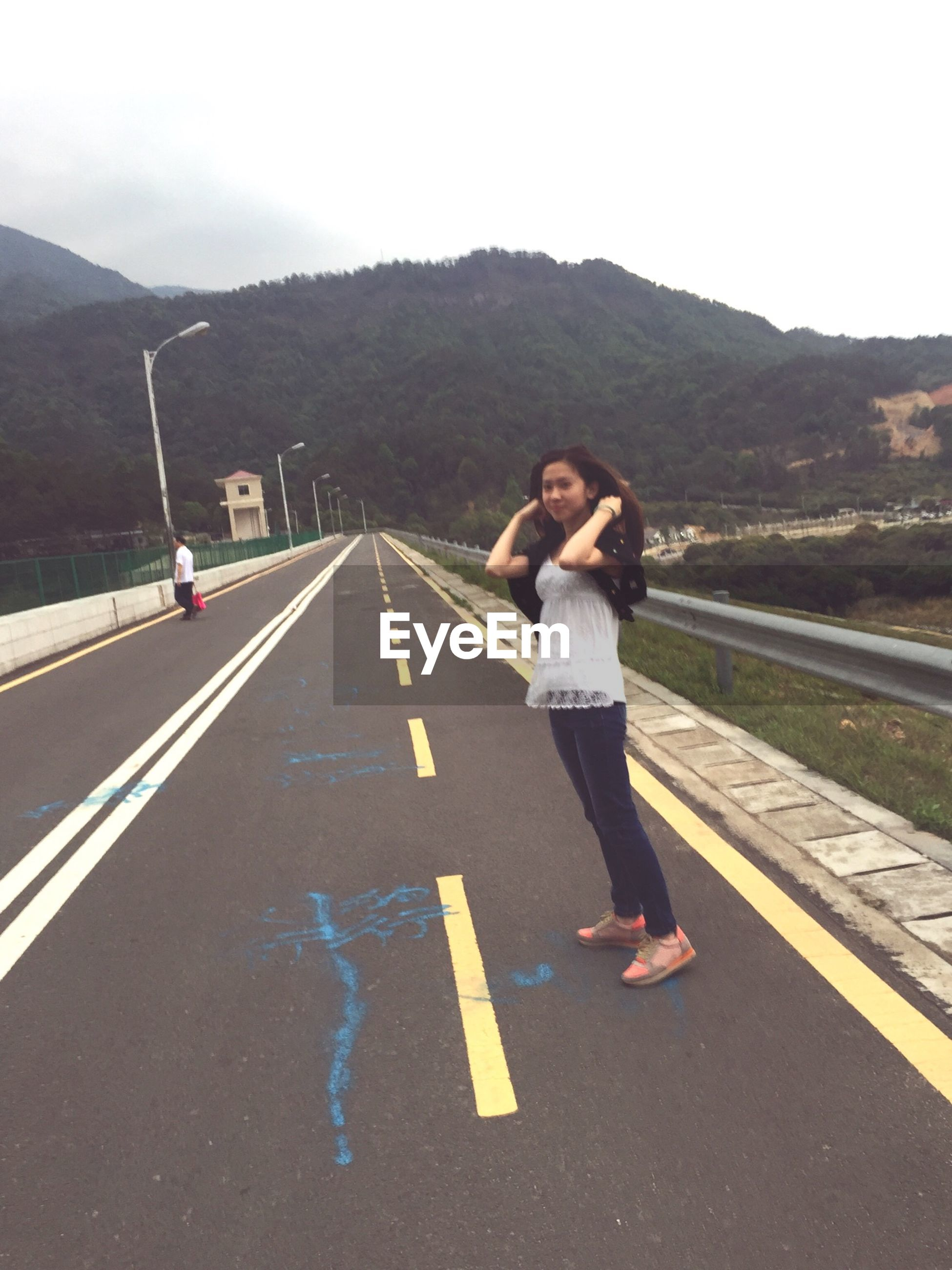 lifestyles, casual clothing, full length, mountain, road, leisure activity, young adult, person, transportation, the way forward, road marking, standing, day, mountain range, front view, street, sky, young men