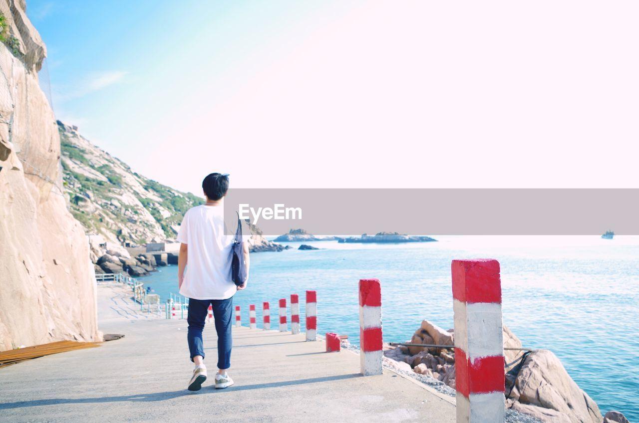 Rear View Of Man Walking On Promenade By Sea Against Sky