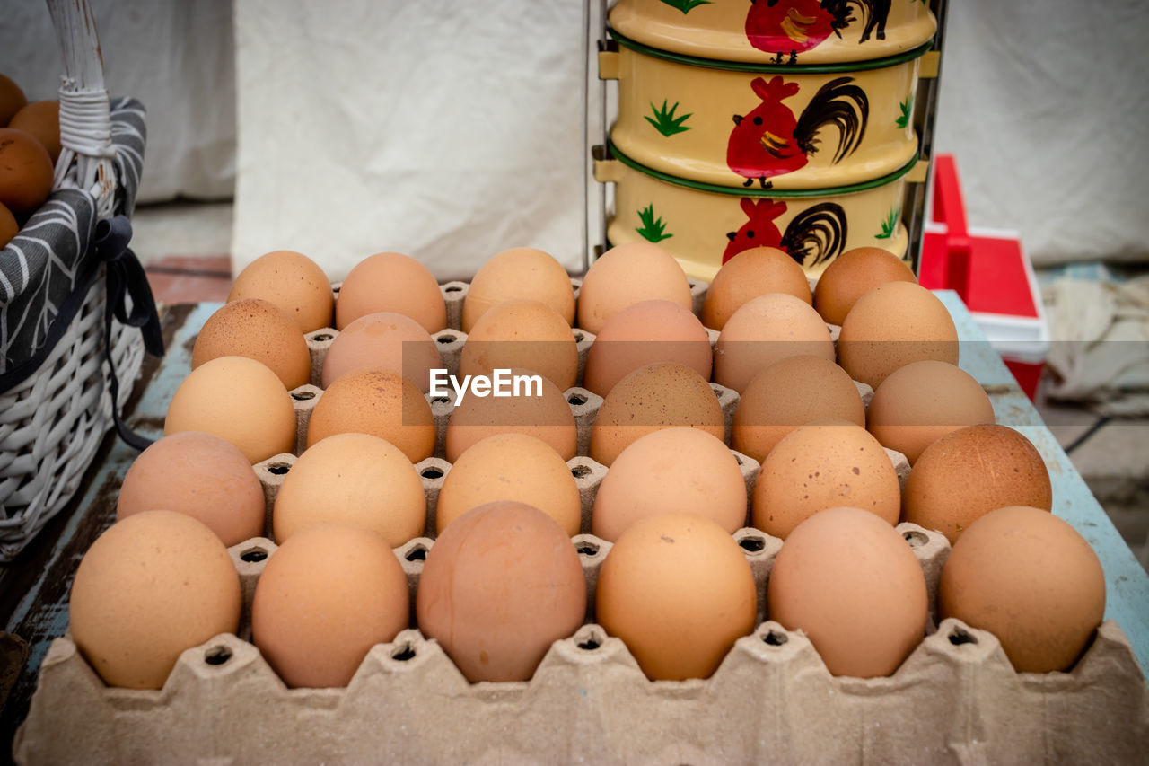 egg, food, food and drink, large group of objects, freshness, container, no people, indoors, raw food, healthy eating, wellbeing, brown, group of objects, close-up, egg carton, market, for sale, still life, in a row, abundance, carton, retail display