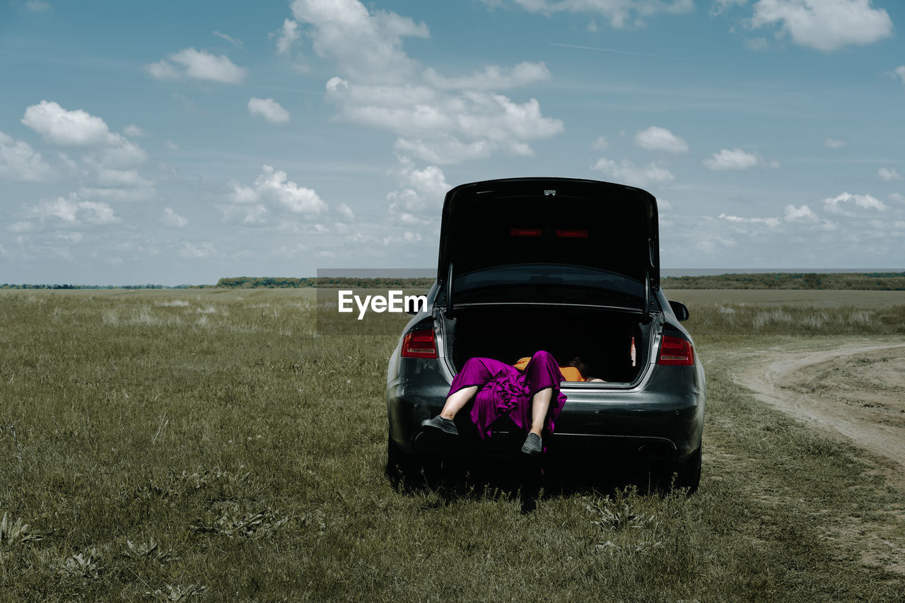 Low section of young woman in car trunk on landscape