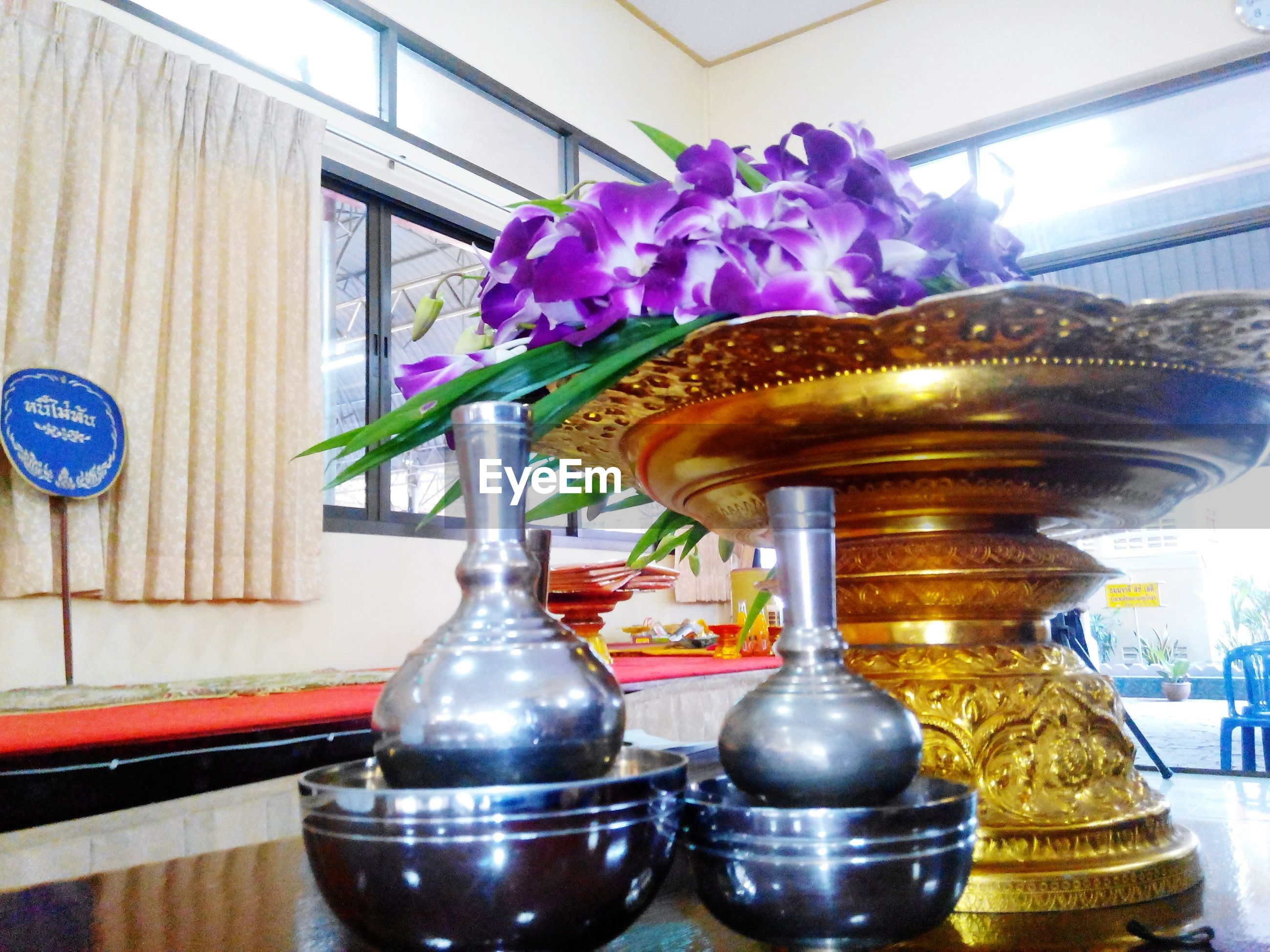 indoors, flower, decoration, art and craft, vase, art, architecture, built structure, creativity, low angle view, potted plant, ornate, no people, flower pot, freshness, glass - material, day, railing, table, religion
