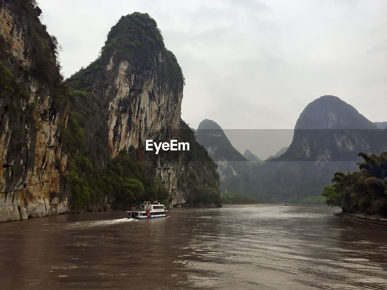 SCENIC VIEW OF RIVER WITH MOUNTAINS IN BACKGROUND