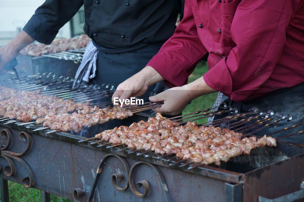 Midsection Of Men Arranging Kebab Skewers On Barbecue Grill