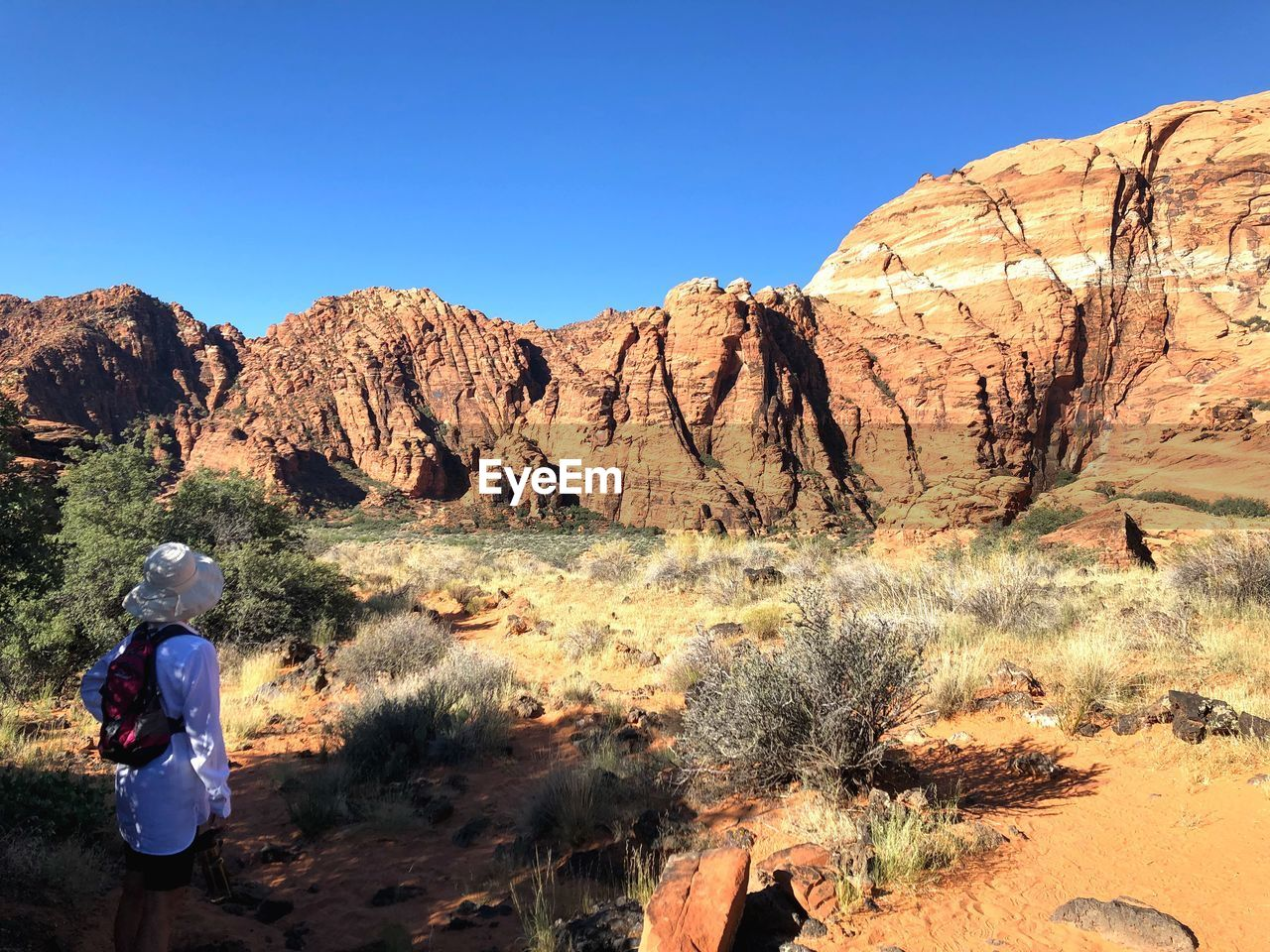 sky, rock, beauty in nature, mountain, clear sky, nature, rock - object, rear view, solid, real people, scenics - nature, non-urban scene, rock formation, environment, tranquility, day, plant, blue, people, sunlight, mountain range, outdoors, formation