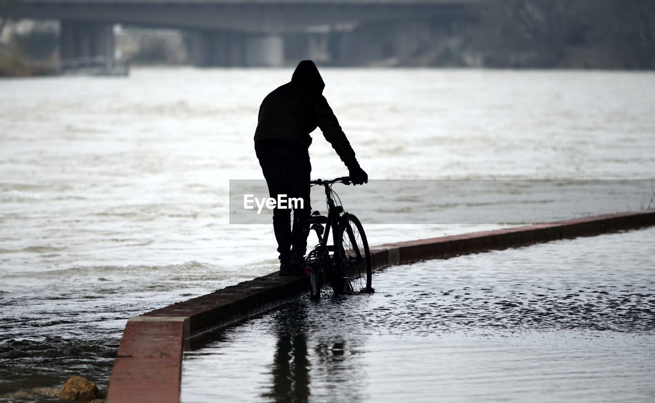 Rear View Of Silhouette Man With Bicycle Walking On Pier At Riverbank