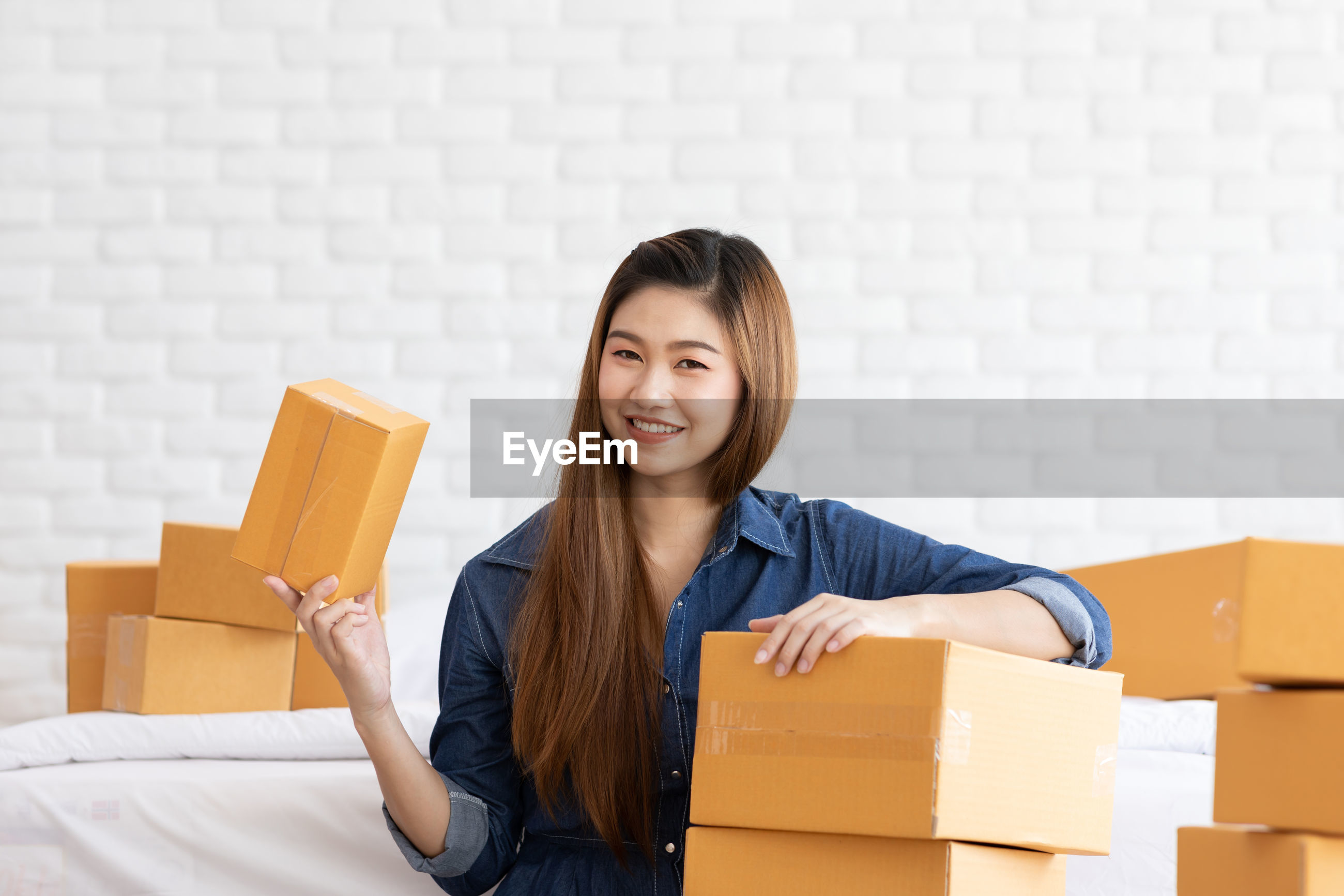 Portrait of smiling woman with boxes at home