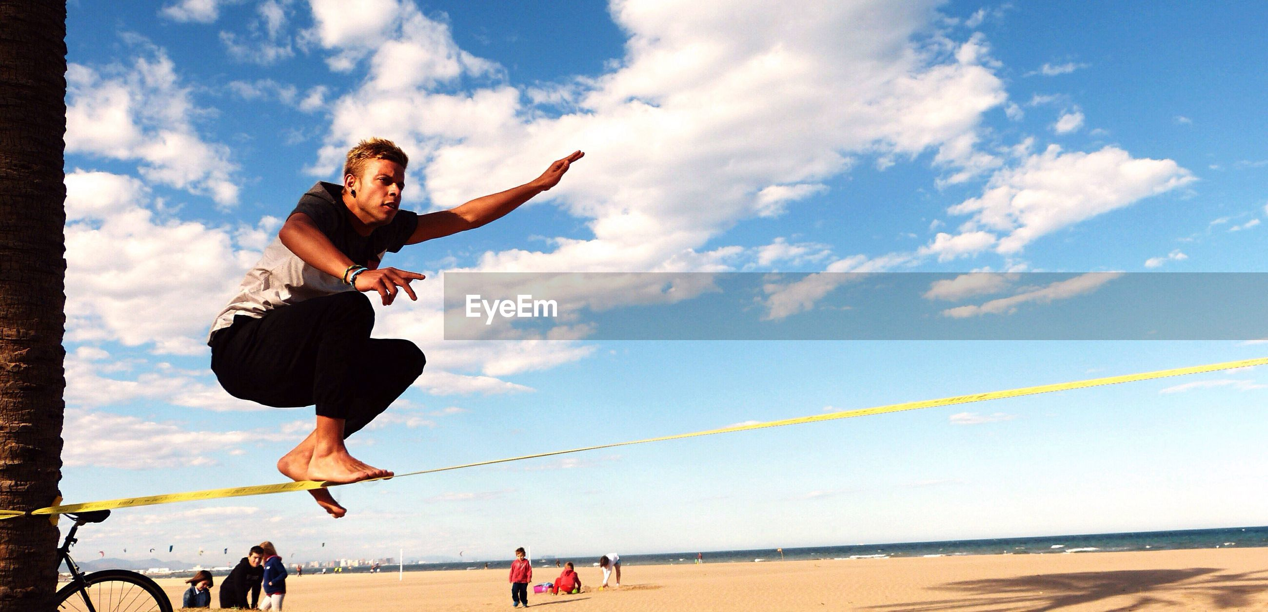 full length, lifestyles, leisure activity, person, casual clothing, young adult, enjoyment, happiness, sky, fun, jumping, young men, beach, playing, mid-air, vacations, arms outstretched