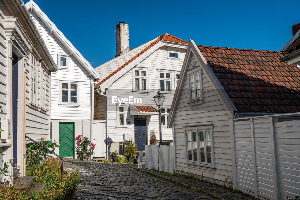 Street Amidst Houses And Buildings Against Blue Sky