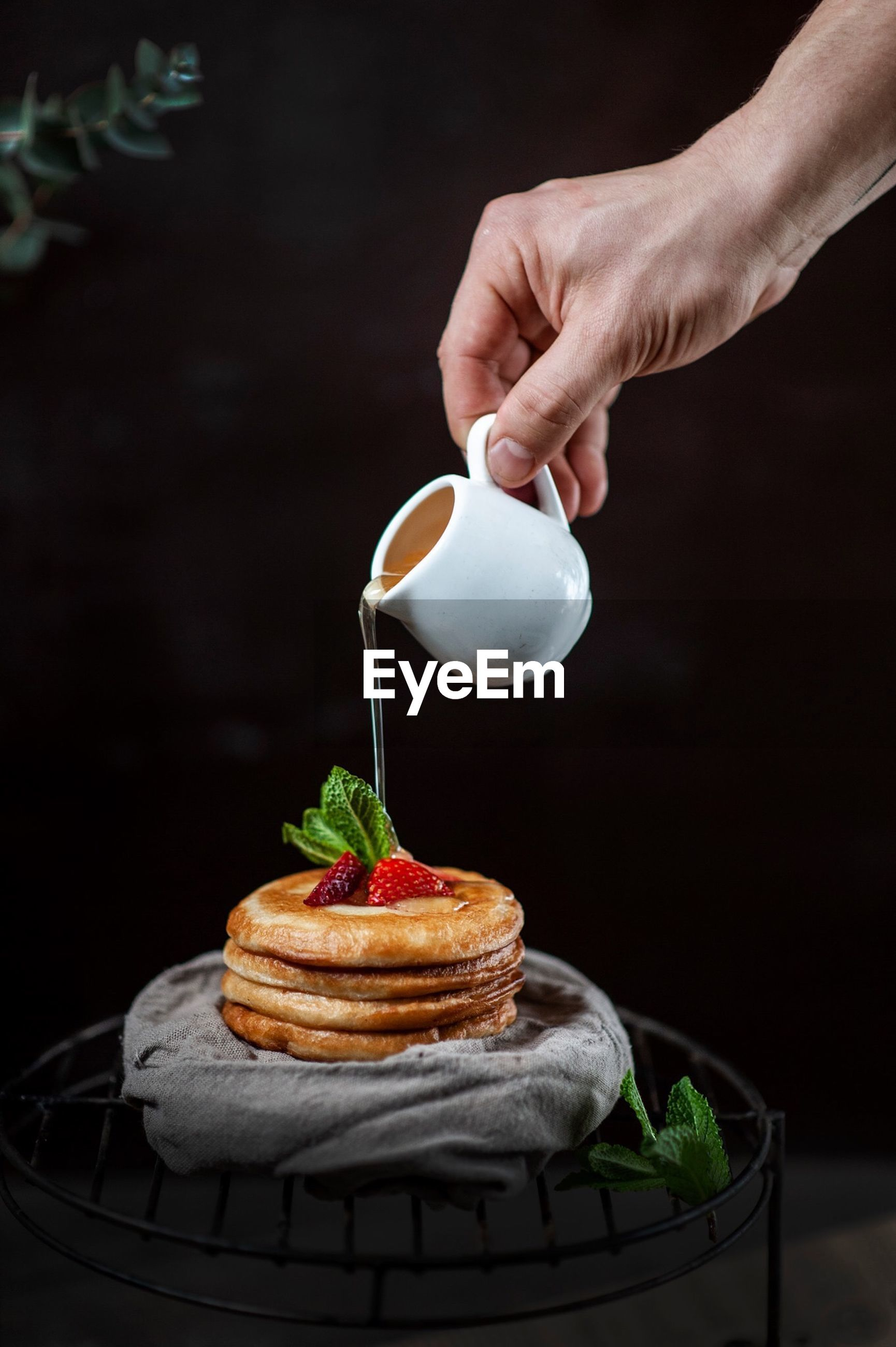 food and drink, food, human hand, freshness, one person, drink, hand, human body part, holding, sweet food, pouring, cup, refreshment, indoors, real people, unrecognizable person, mug, indulgence, ready-to-eat, baked, temptation, finger