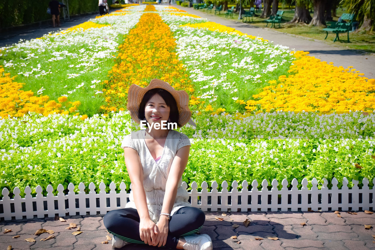 one person, young adult, looking at camera, portrait, young women, leisure activity, front view, plant, smiling, real people, sitting, lifestyles, women, casual clothing, yellow, beautiful woman, full length, flower, adult, outdoors, hairstyle