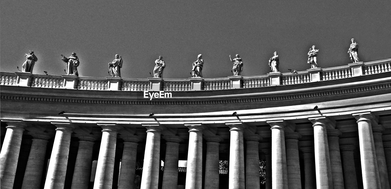 Low Angle View Of Statues At St Peter Basilica Against Clear Sky