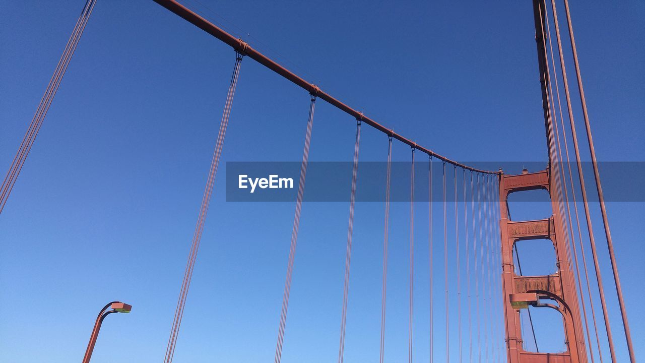 sky, low angle view, clear sky, blue, architecture, day, nature, built structure, no people, connection, metal, cable, bridge, transportation, bridge - man made structure, suspension bridge, outdoors, industry, construction industry