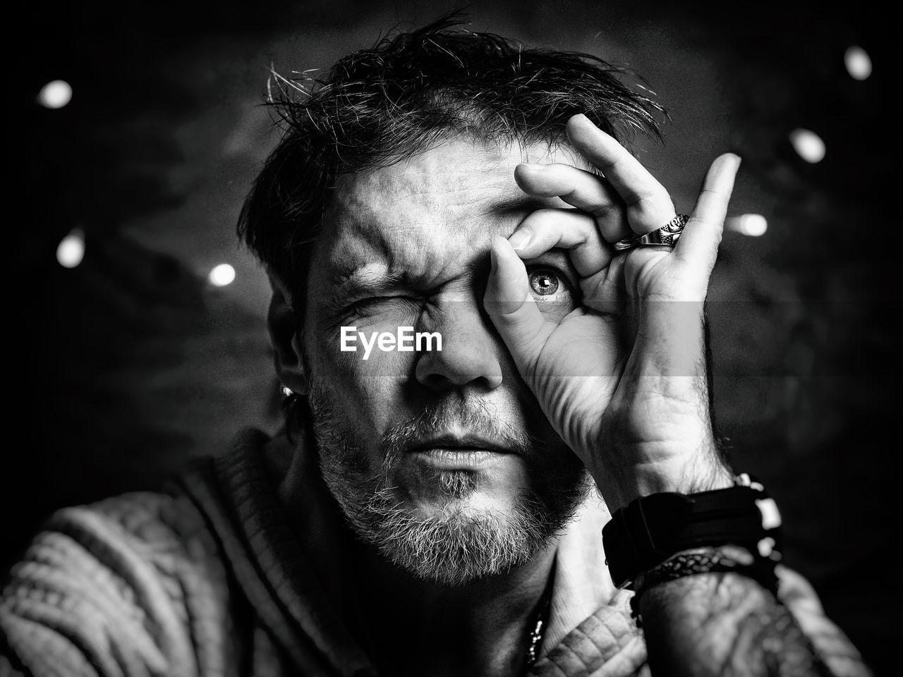 Close-Up Of Man Making Circle Around Eye With Hand