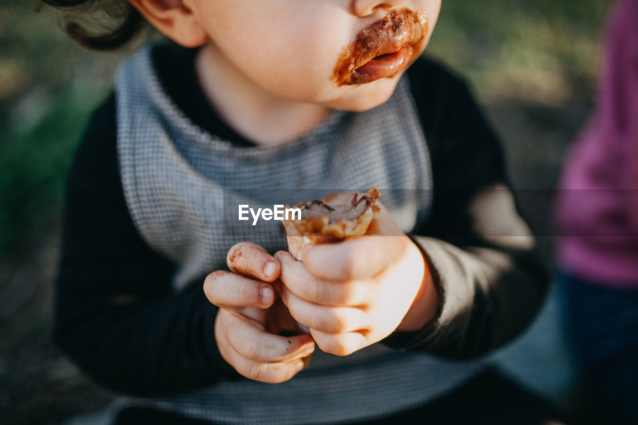 Midsection of child eating chocolate icecream