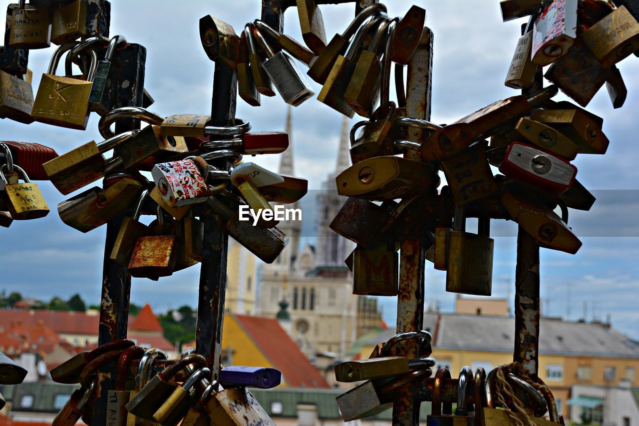 Padlocks Attached On Railing With Historic Building In Background