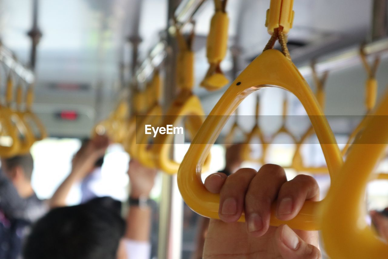 Close-Up Of Hand Holding Handle Hanging In Train