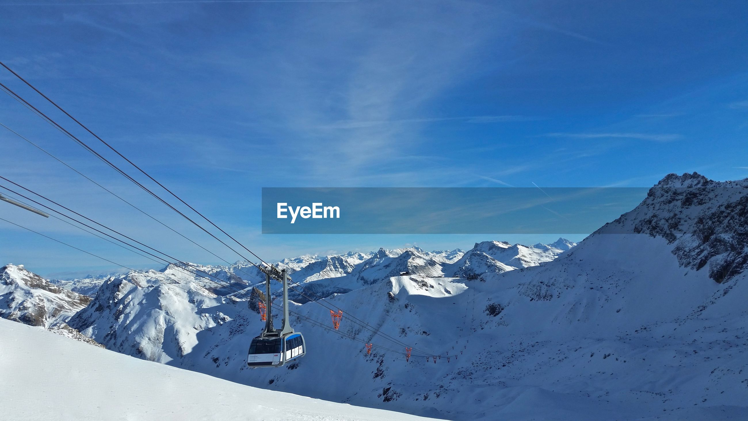 Ski lift over snowcapped mountains against blue sky