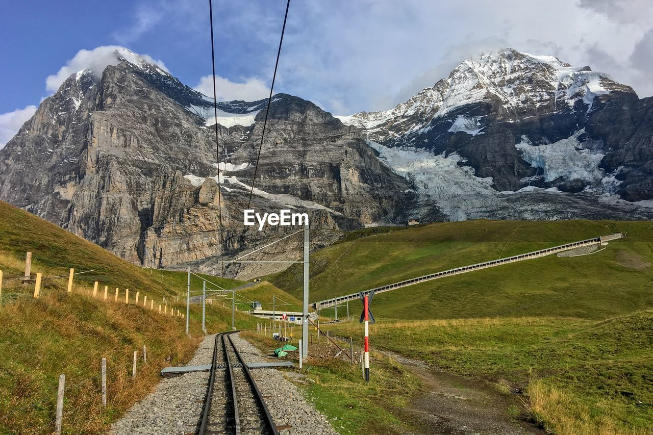 mountain, transportation, scenics - nature, beauty in nature, mountain range, landscape, rail transportation, environment, nature, railroad track, winter, sky, snow, grass, cloud - sky, no people, track, direction, day, snowcapped mountain, outdoors, electricity, mountain peak