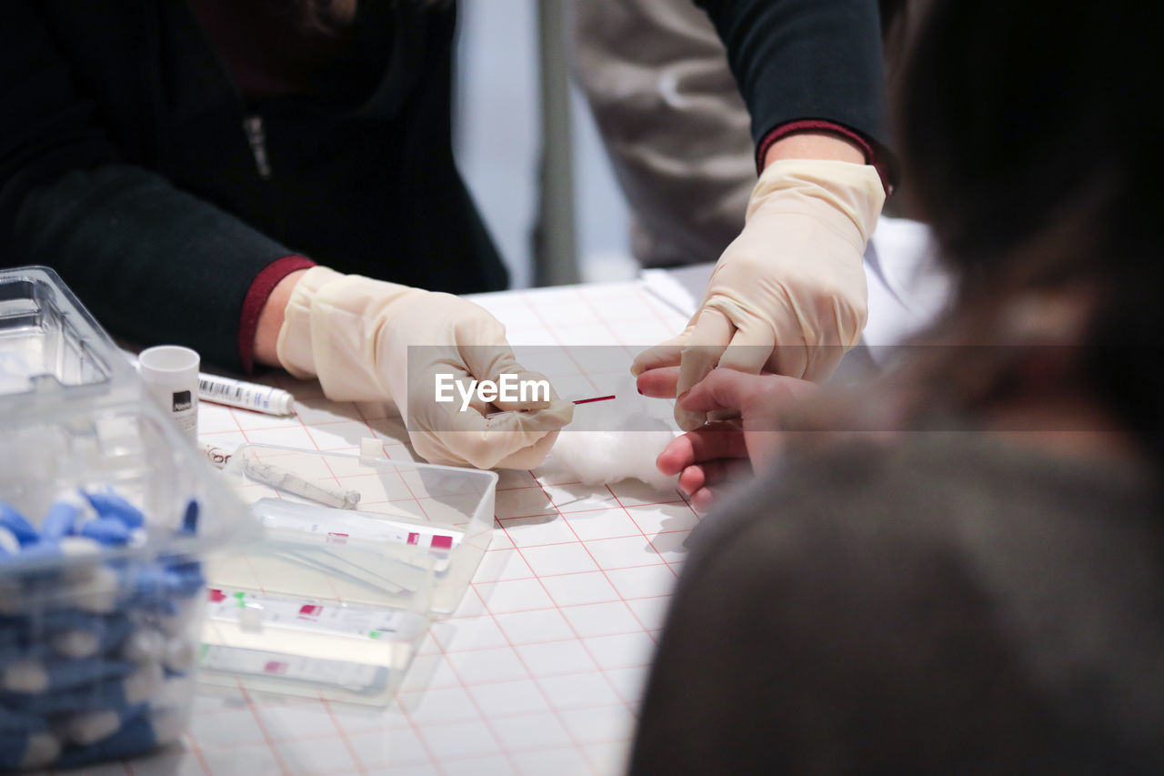 Midsection of female doctor removing patient blood in hospital