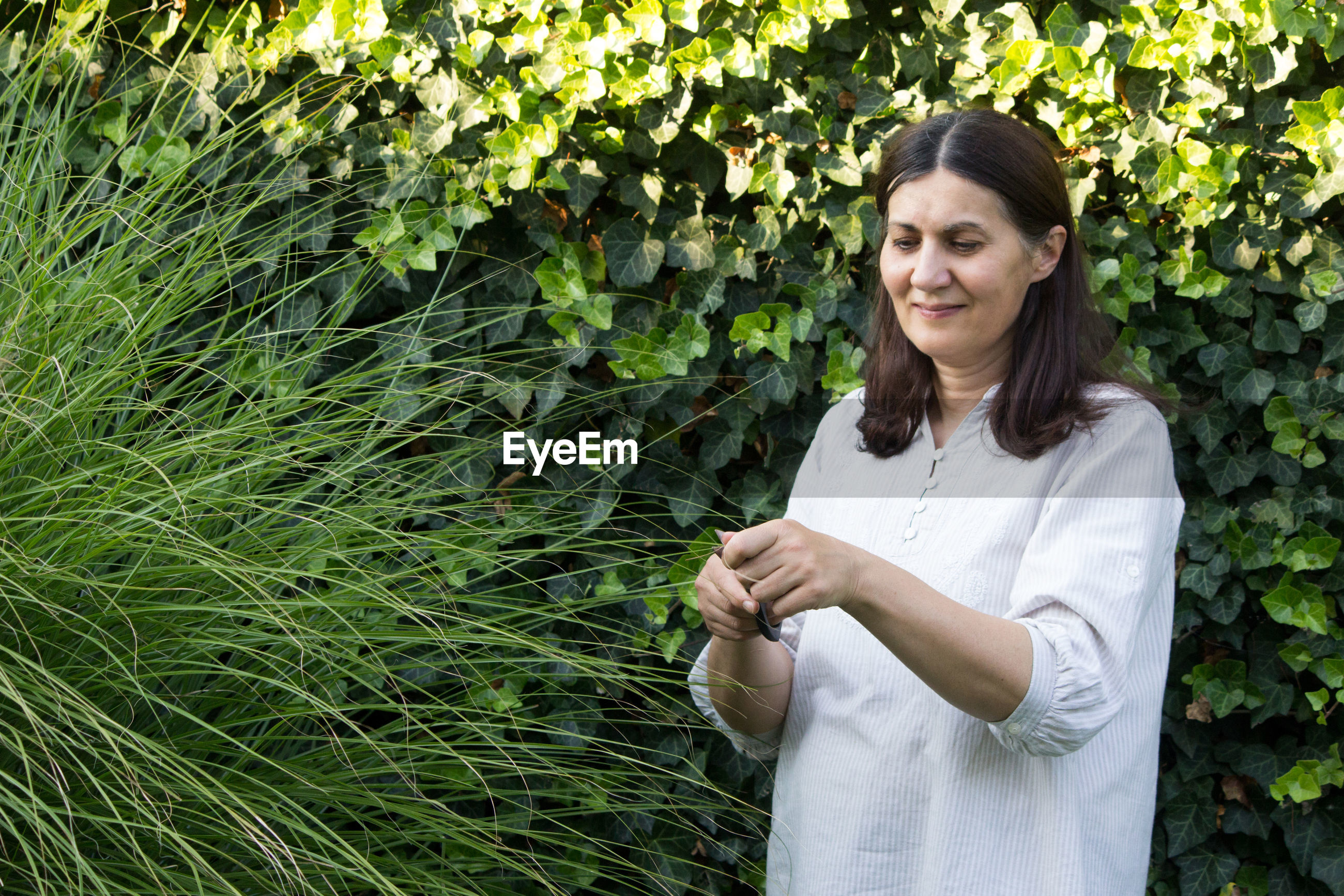 Smiling woman cutting while standing by plants