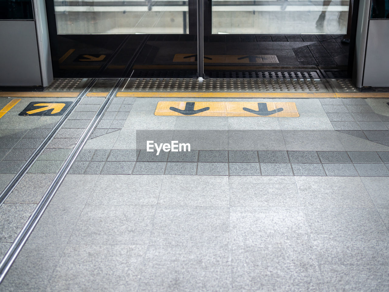 communication, indoors, number, flooring, text, sign, transportation, tiled floor, no people, entrance, door, tile, day, high angle view, public transportation, mode of transportation, absence, yellow, western script, station