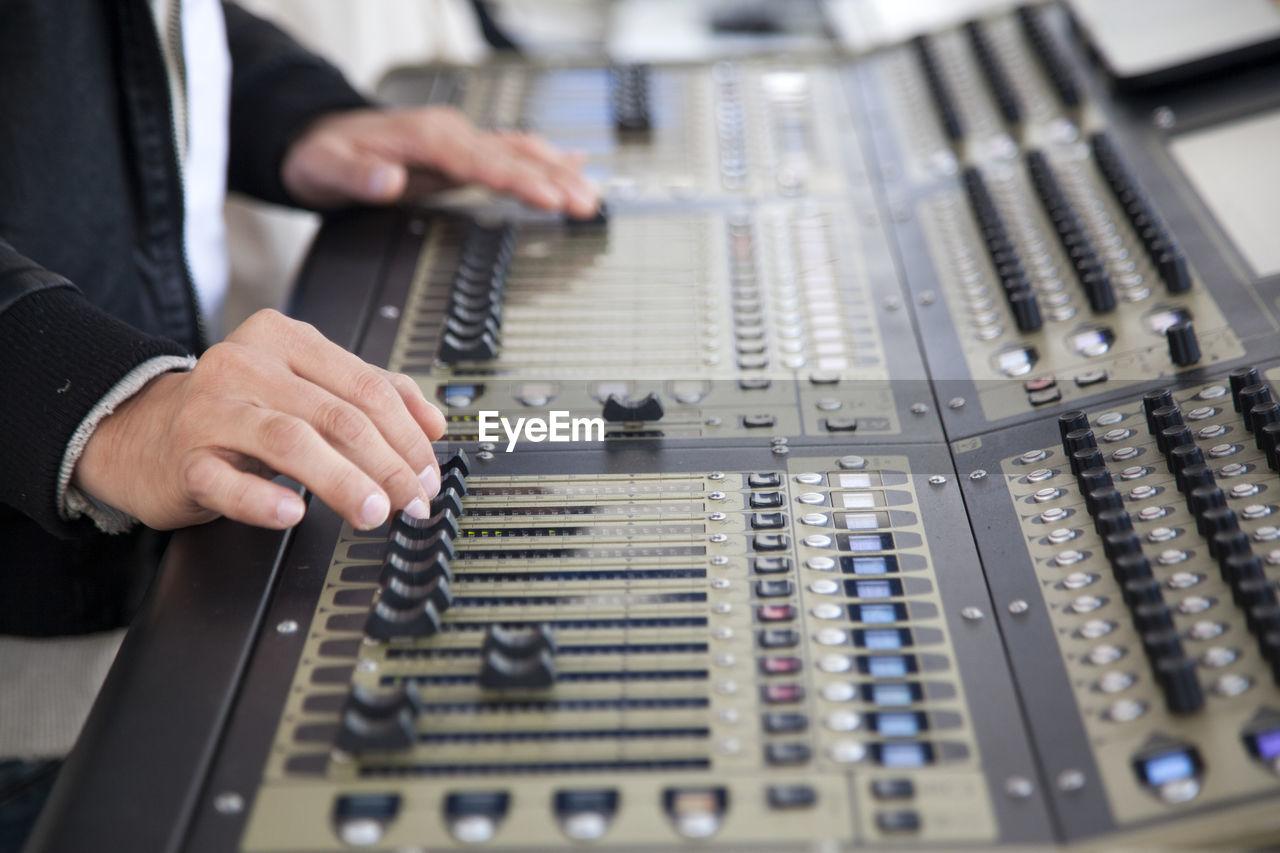 Technician Adjusting Sound Mixers At Studio