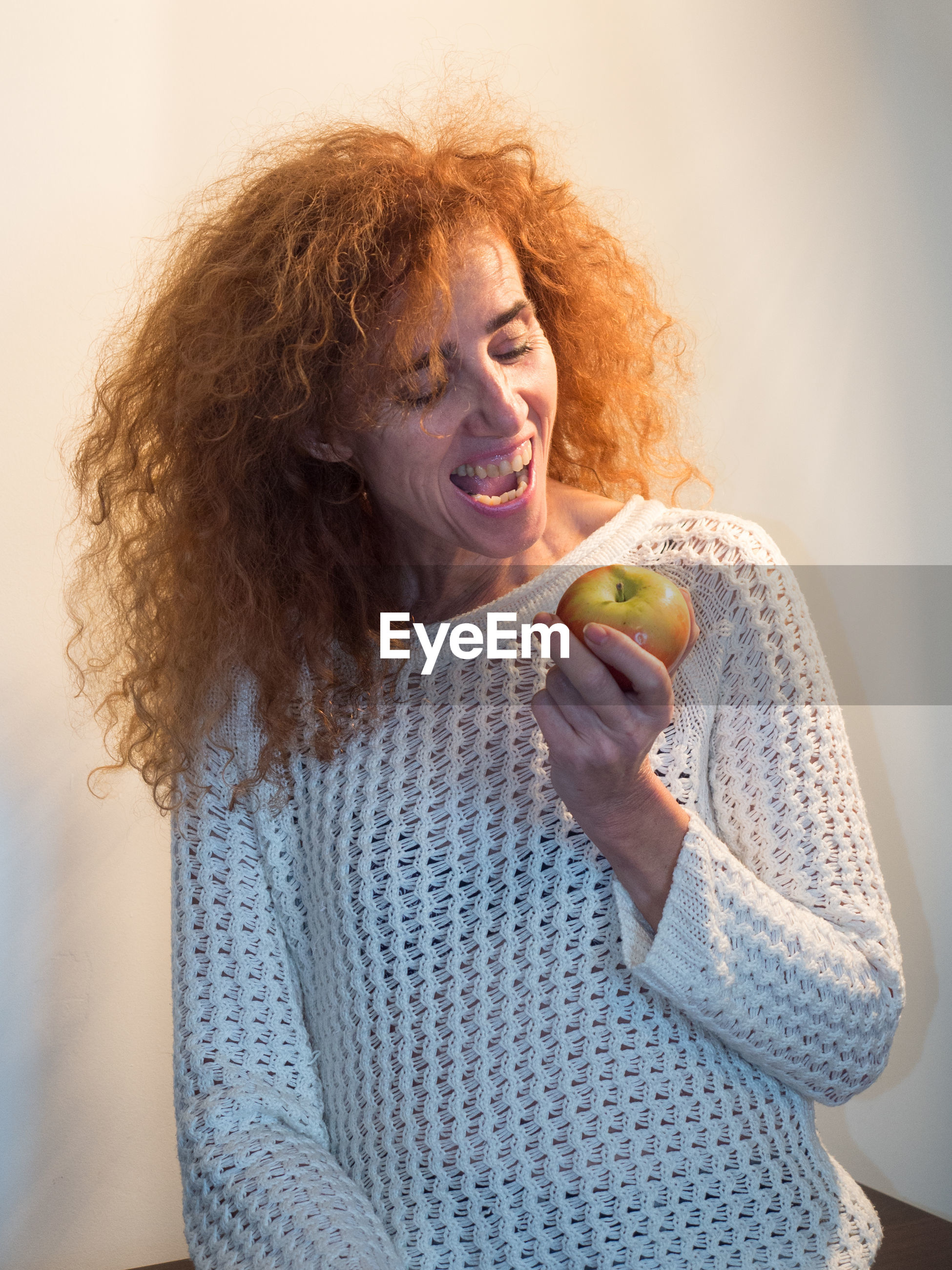 Mature woman eating apple against wall