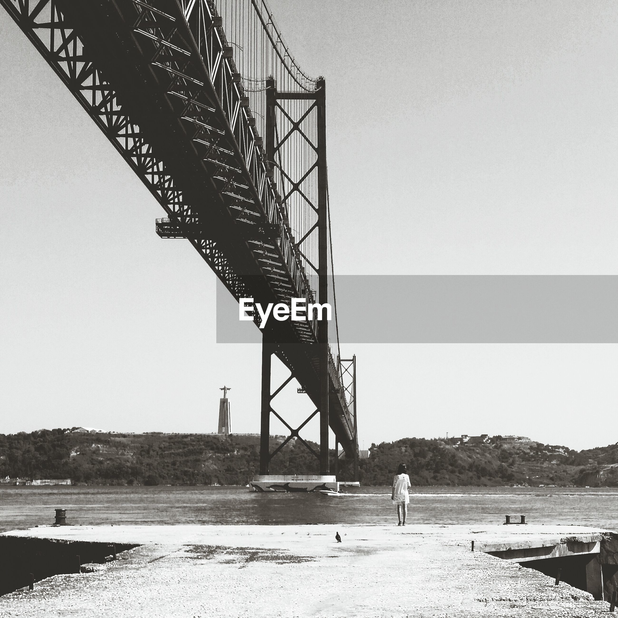 Rear view of woman standing by april 25th bridge and tagus river against sky