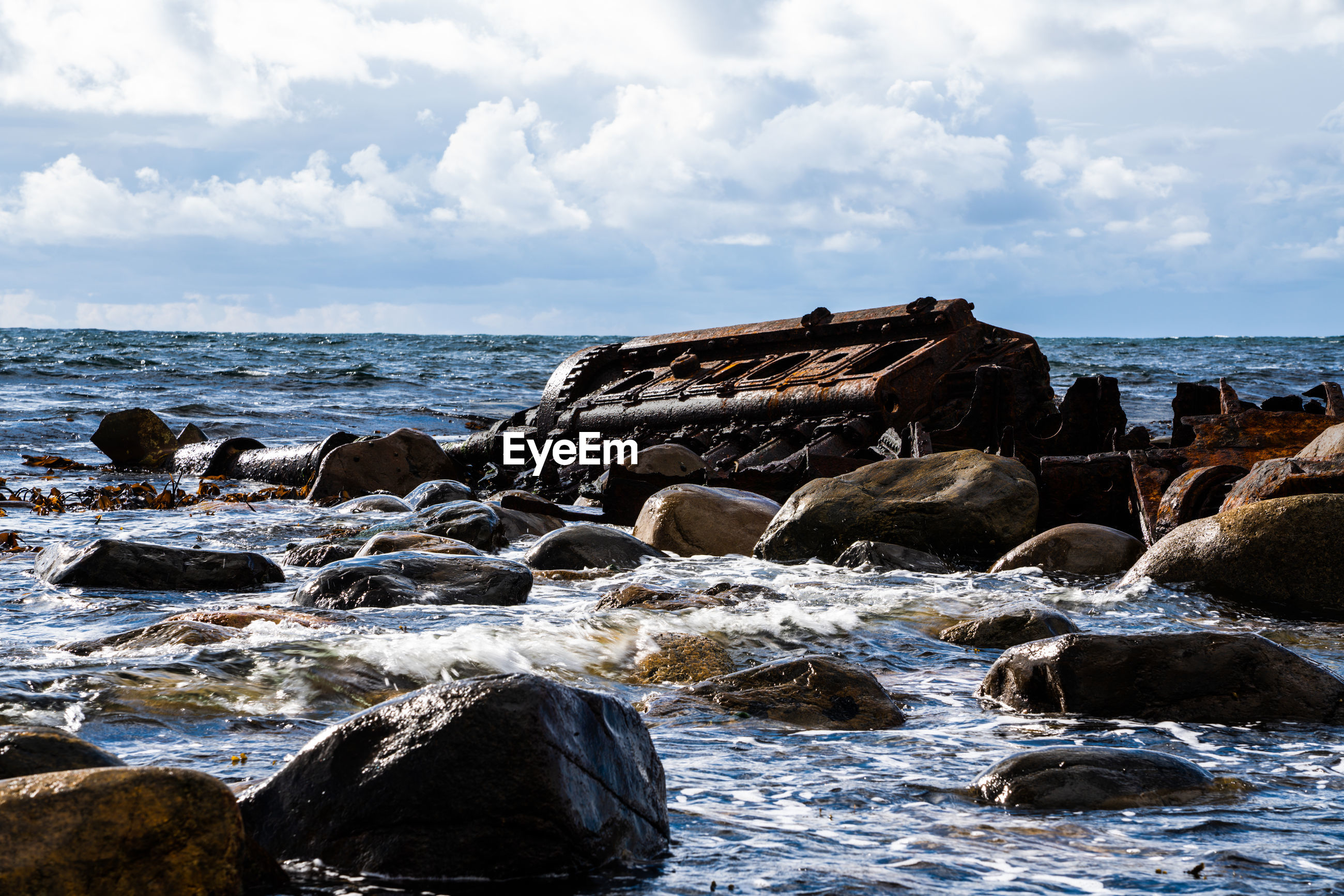 SCENIC VIEW OF ROCKS ON SHORE AGAINST SKY