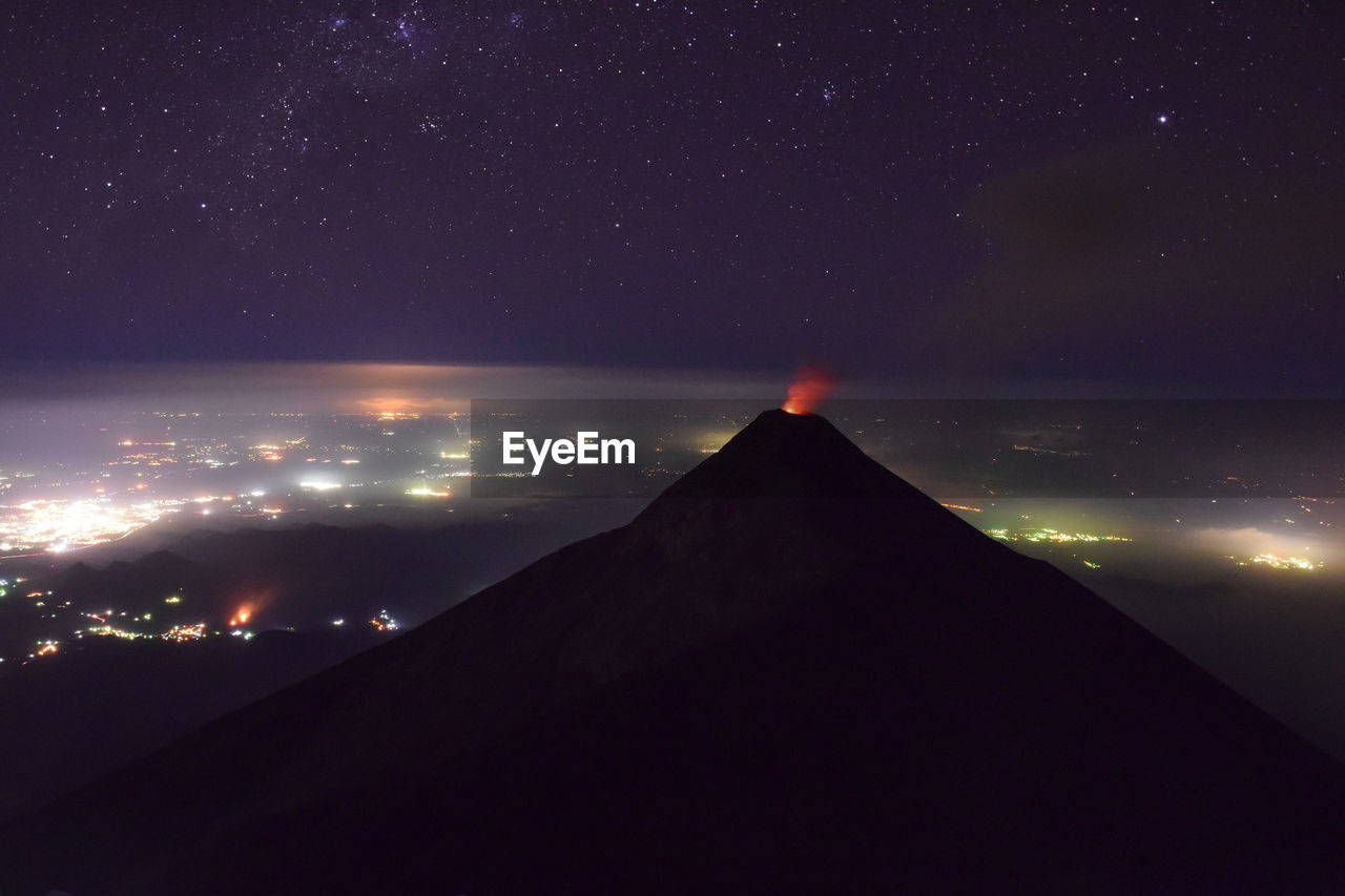 View of mountain and illuminated townscape against star field