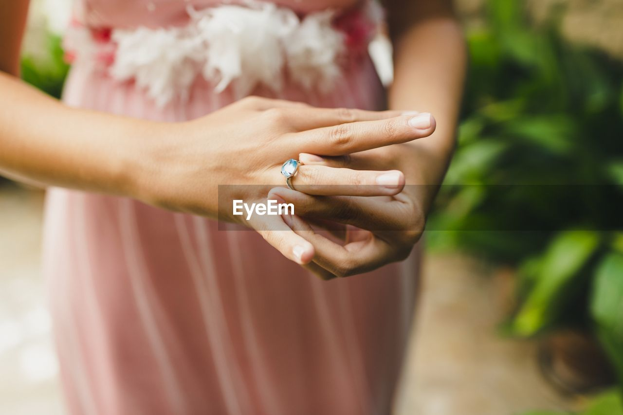 midsection, hand, human hand, women, wedding, real people, adult, ring, jewelry, bride, newlywed, human body part, people, holding, event, focus on foreground, standing, wedding ring, celebration, married, couple - relationship, body part, positive emotion, wedding ceremony, finger