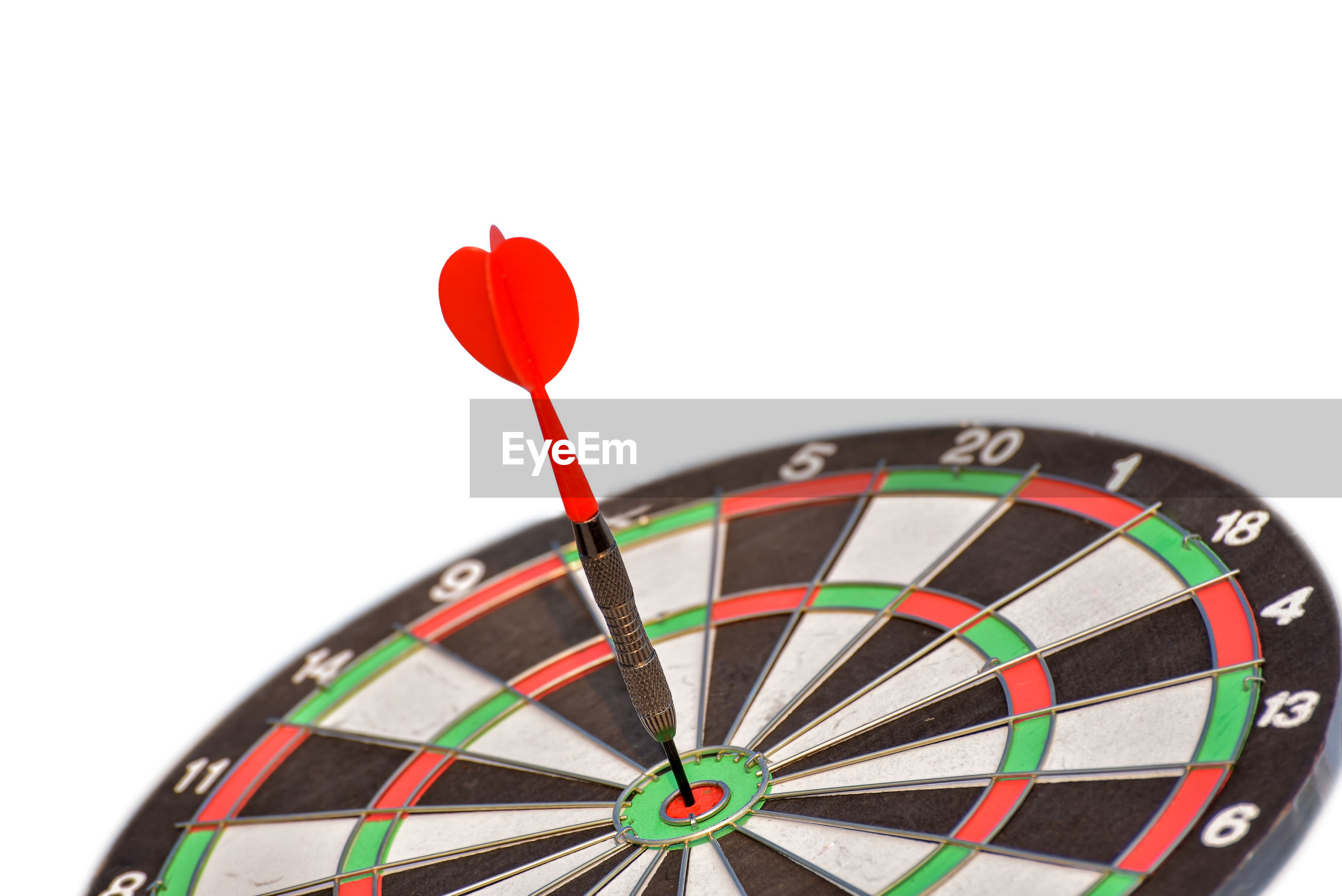 Close-up of dart in dartboard over white background