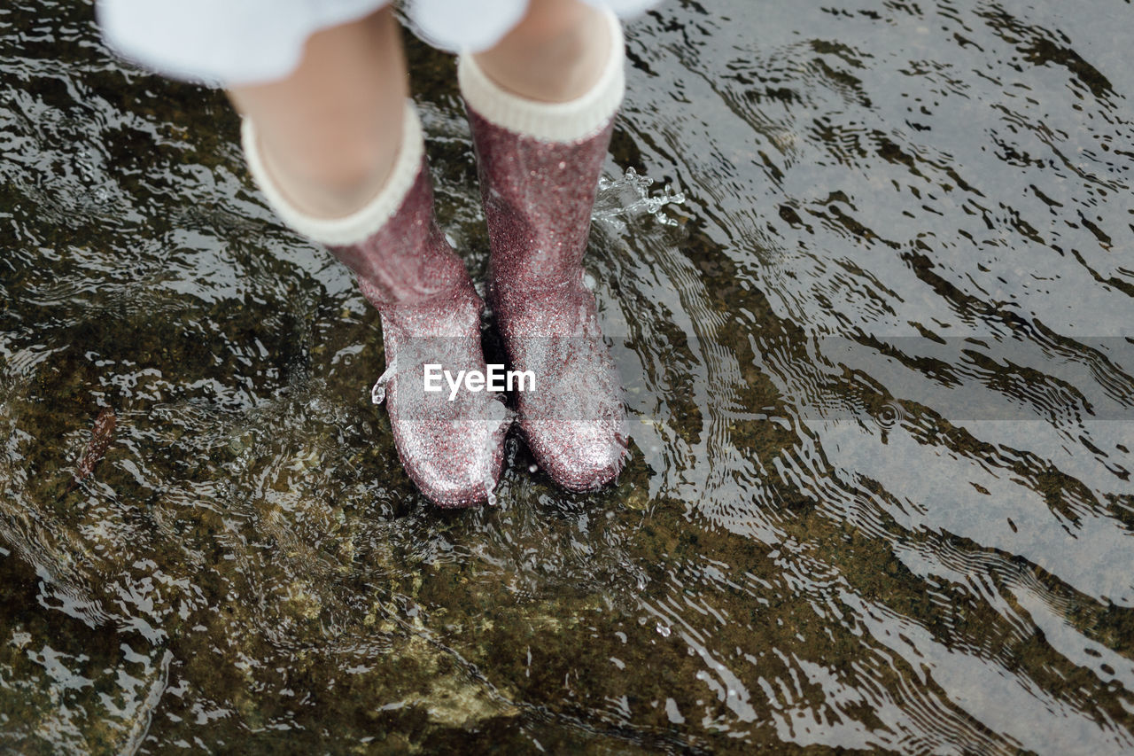 Low Section Of Woman Standing On Puddle