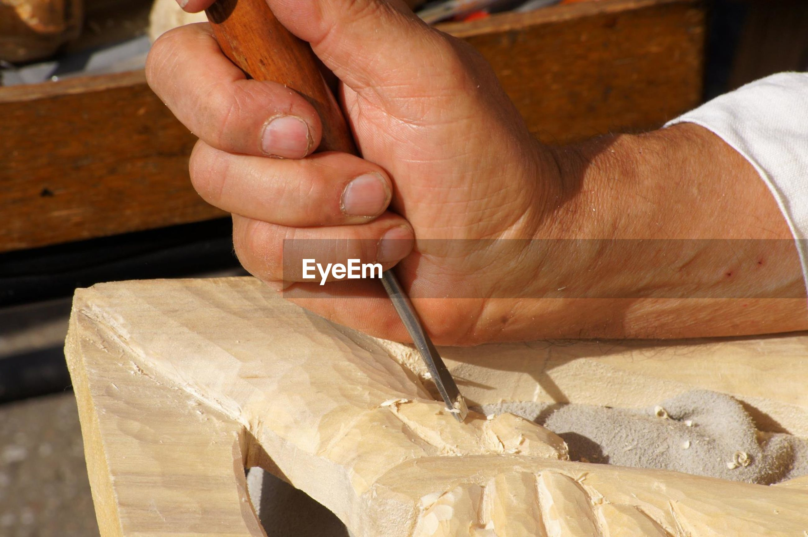 Cropped image of craftsperson carving wood at workshop