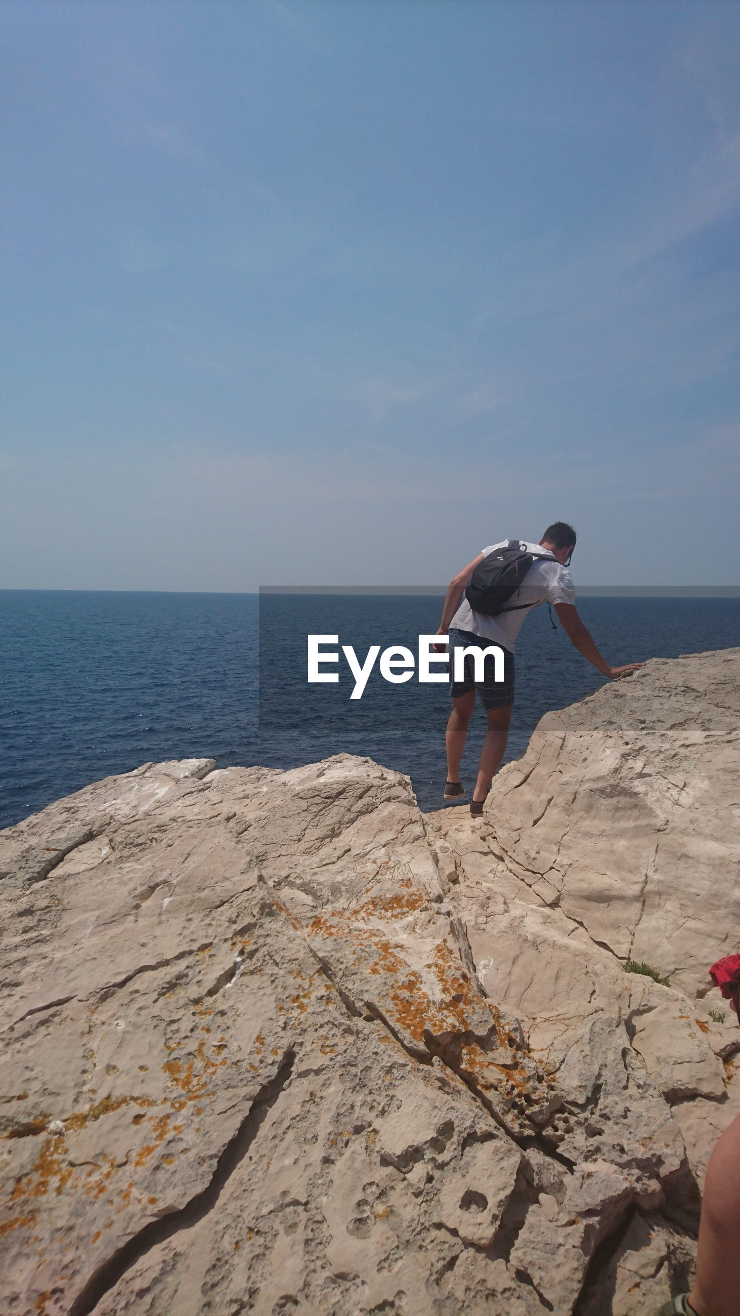 REAR VIEW OF MAN STANDING ON ROCK AT BEACH