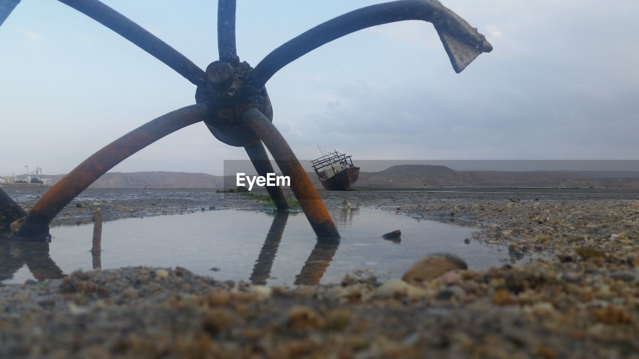 water, sky, nature, sea, metal, beach, no people, transportation, land, day, outdoors, selective focus, cloud - sky, close-up, rusty, mode of transportation, anchor - vessel part, nautical vessel, focus on background, wheel
