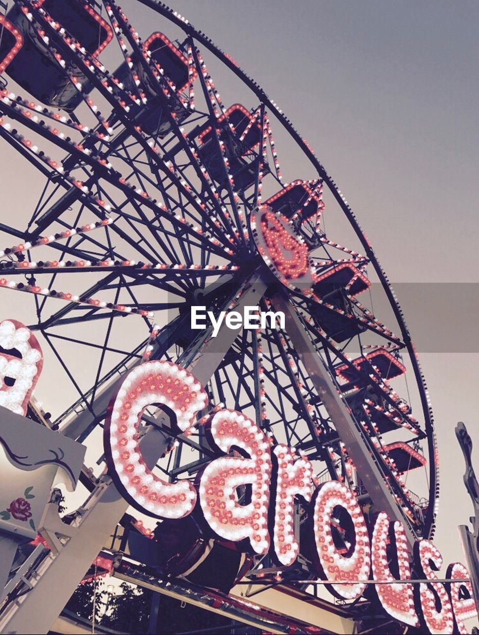 ferris wheel, amusement park, arts culture and entertainment, amusement park ride, low angle view, no people, rollercoaster, big wheel, outdoors, day, clear sky, sky, architecture, close-up