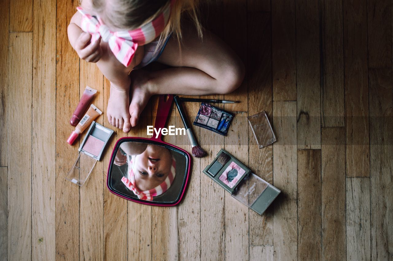 Directly above shot of girl playing with beauty products on hardwood floor
