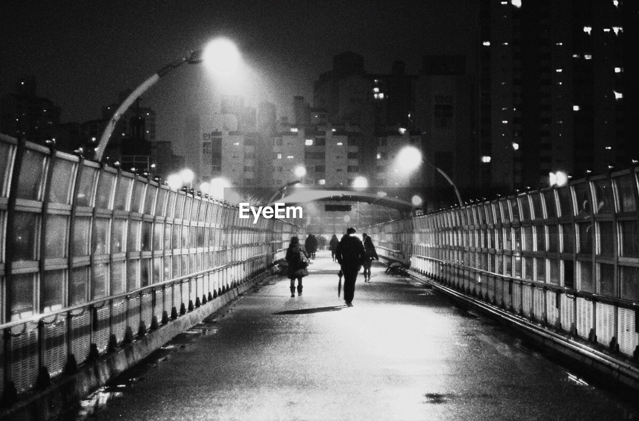 walking, full length, architecture, illuminated, built structure, rear view, the way forward, men, night, building exterior, lifestyles, city, lighting equipment, city life, person, street light, railing