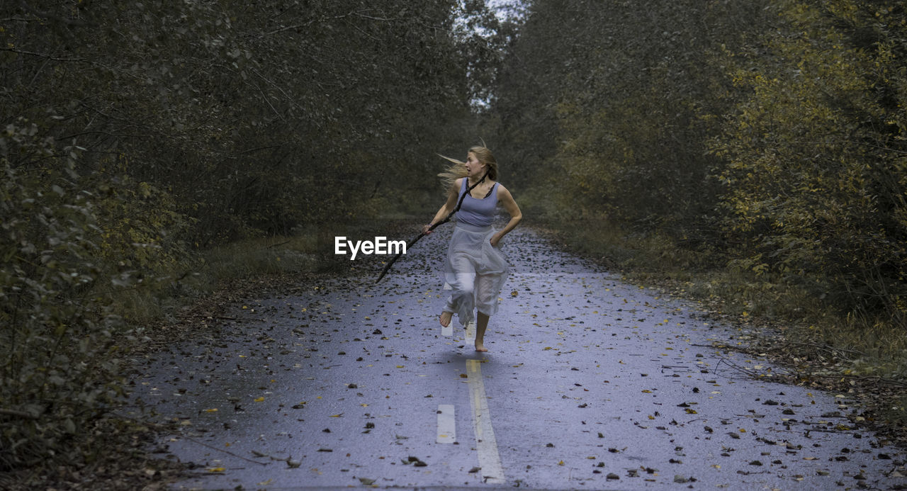 Scared Young Woman Running On Footpath In Forest
