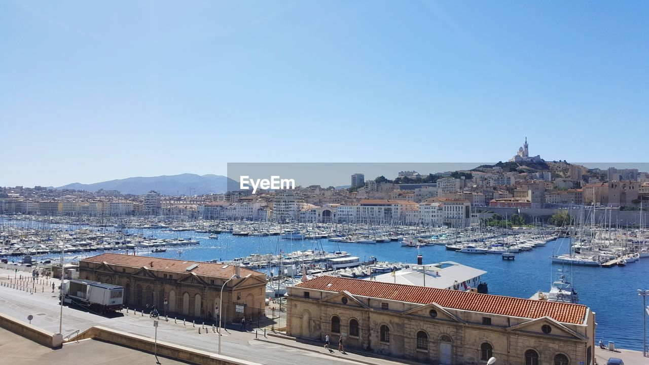 building exterior, architecture, built structure, water, sky, nautical vessel, city, clear sky, building, copy space, nature, transportation, day, harbor, high angle view, residential district, no people, blue, mode of transportation, sailboat, cityscape, outdoors, yacht, port, bay, townscape, marina