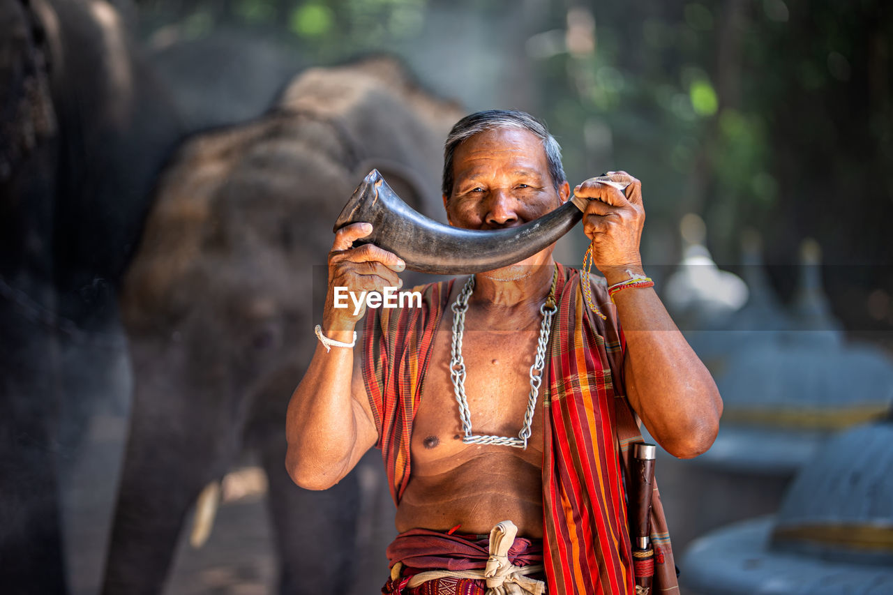 Man holding horn in forest